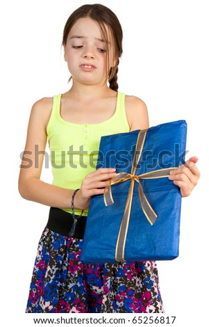 A primary aged girl looks disappointed to receive a ribbon wrapped gift. - stock photo