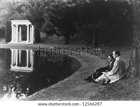 A print from a glass negative taken in an an old view camera about 1890. Two men sitting by pond with gazebo in background. - stock photo