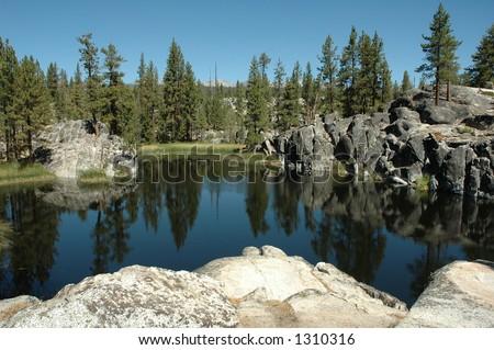 A pristine alpine lake in the western Sierra Nevada Mountains of California. - stock photo