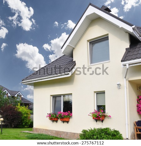 a private house with a garden in a rural area under beautiful sky - stock photo