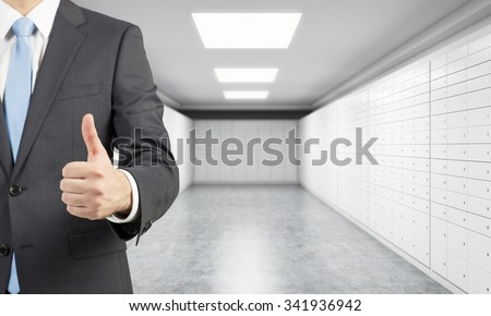 A private manger of a bank with thumb up stands in a room with safe deposit boxes. A concept of storing of important documents or valuables in a safe and secure environment. - stock photo