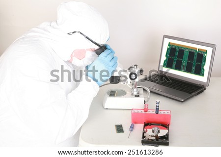 A Professional Computer Forensics Technician examines Computer Micro Chips under his microscope for microscopic damage and for information recovery of important and secret documents for clients.  - stock photo