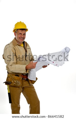 A professional male construction contractor worker wearing a hard hat and tool belt is holding construction blue print plans. - stock photo