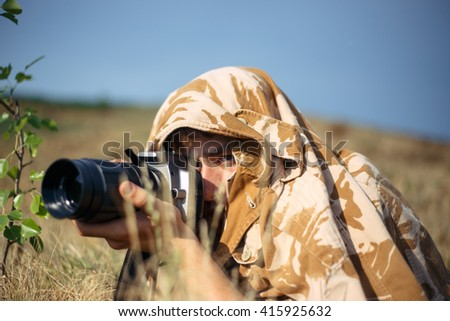 A professional nature/wildlife photographer at work. Man is shooting foxes at meadow. He covered by shirt from the camouflage fabrics. Camouflage shirt make his invisible in the grass. - stock photo