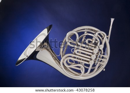 A professional silver French horn isolated against a spotlight blue background. - stock photo