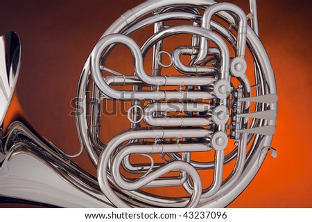 A professional silver French Horn isolated on a spotlight gold background. - stock photo