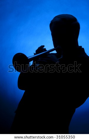 A professional trumpet player in silhouette against a blue background in the vertical format with copy space. - stock photo