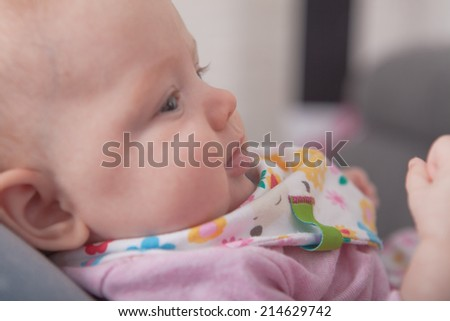A profile picture of a little baby laying on her momms feet. - stock photo