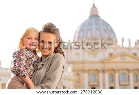 A proud and loving mother looking at the camera holds her blonde daughter in her arms. Both are smiling and happy about touring Italy and Vatican City. In the background is St. Peter's Basilica. - stock photo