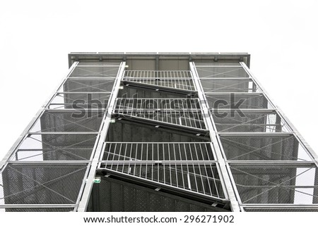 A public metal fire staircase tower in a yard on white sky - stock photo