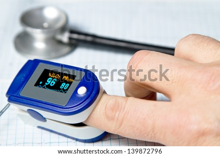 A pulse oximeter used to measure pulse rate and oxygen levels with medical stethoscope and ECG background - stock photo