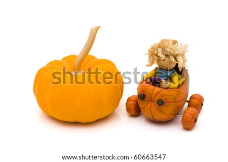A pumpkin with a little scarecrow driving a pumpkin isolated on white, autumn - stock photo