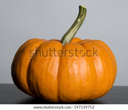 A pumpkin with a long stalk on a table.