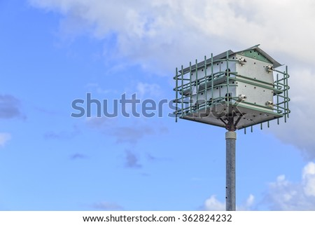 A purple martin bird house with copy space.