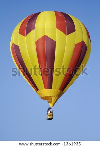 A purple, red, and yellow striped hot air balloon drifts silently across a clear blue sky.