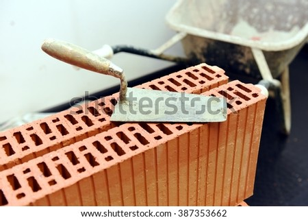 A putty knife or mason's trowel resting on a stack of bricks after a construction of a wall with wheelbarrow in the background. Inside of a building site room before a masonry work. - stock photo