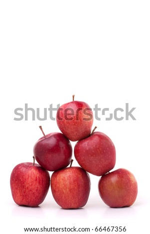 A pyramid of red delicious apples on a white background.