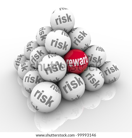 A pyramid of stacked balls each marked Risk with one reading Reward symbolizing the hidden benefits of taking a risk and overcoming a challenge with a great return on your investment of effort - stock photo