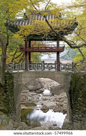 A quaint little bridge near a Korean temple hidden in the Autumn (Fall) foliage. - stock photo