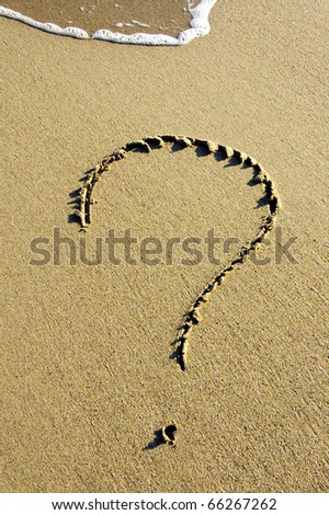 a question mark drawn on the sand of a beach