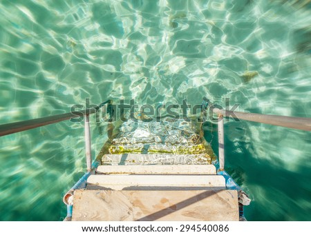 a quick jump from the dock into the clean sea water - stock photo