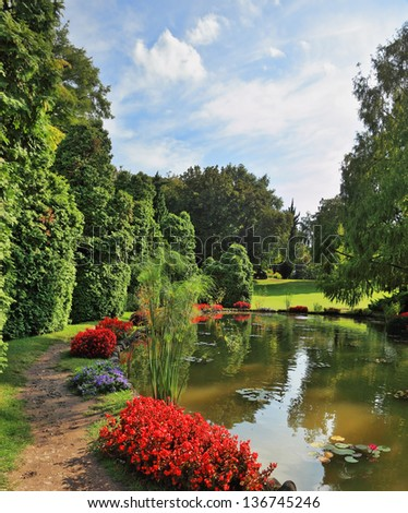 A quiet corner of the picturesque park in Europe. A pond, overgrown with lilies  and red flower beds