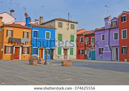 A quiet square in the middle of colourful houses on the island of Burano in the Venice lagoon, Italy - stock photo