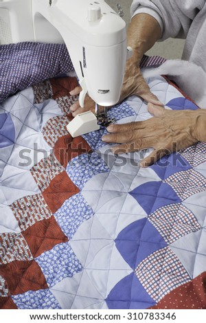 A quilter finishes grid pattern on a patriotic quilt.