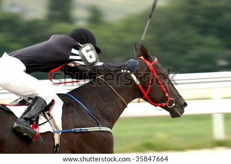 A racehorse and jockey cross the finish line first in a horse race. - stock photo