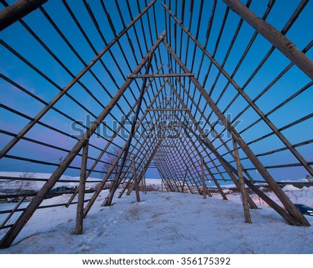 A rack for drying stockfish at sunrise