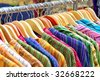 A rack of colorful shirts hanged for sale at a fair - stock photo
