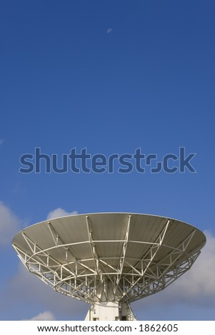 A radio telescope points into an early morning sky where the moon is still present - stock photo