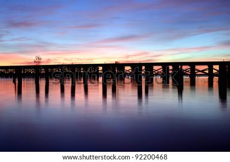 a railroad bridge crossing a river before sunrise - stock photo