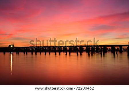 a railroad bridge over a river at sunrise - stock photo