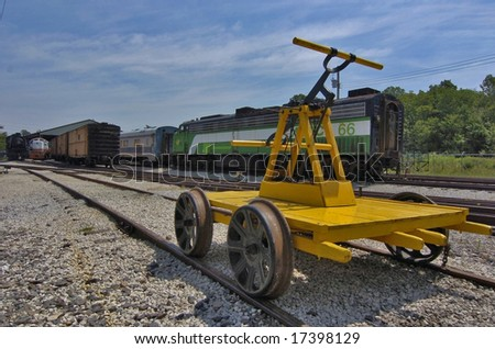 A railroad handtrolly awaits its driver at a rail yard.