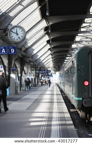 A Railroad-station with interesting lighting and a train waiting for departure - stock photo