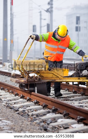 a railroad worker grinds the rails with his machine - stock photo