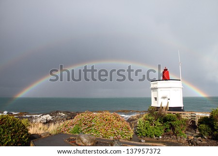 A rainbow behind Stirling Point Lighthouse with stormy weather on the way at Bluff, New Zealand - stock photo