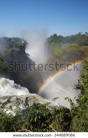 A rainbow over Victoria Falls, Zimbabwe - stock photo
