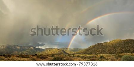 A rare double rainbow appears over Albuquerque's Sandia Mountains in the monsoon season - stock photo
