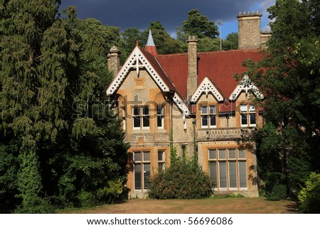 A rather dramatic image of a large period family home surrounded by woodland - stock photo