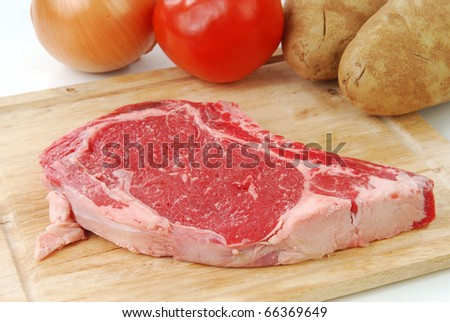 A raw ribeye steak on a cutting board with vegetables - stock photo