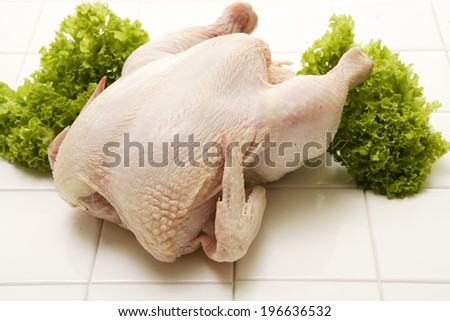 A raw whole chicken garnished with parsley on an isolated white background - stock photo
