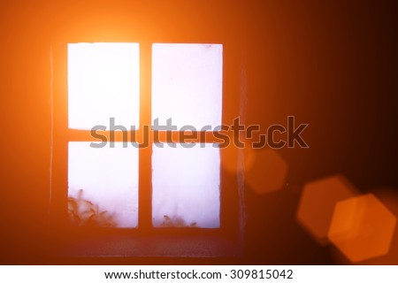 A ray of morning sun in an old window - stock photo
