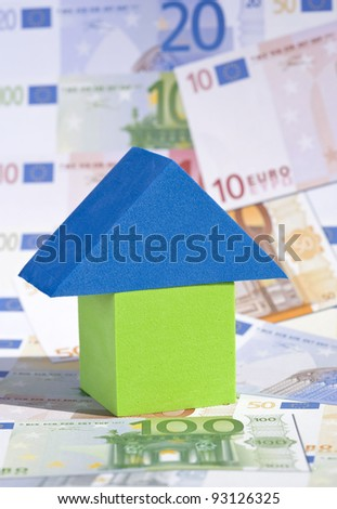 A real estate investment concept with a toy house surrounded by Euro banknotes - stock photo