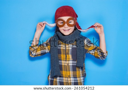 A real pilot. Playful little boy wearing and smiling while standing against blue background - stock photo