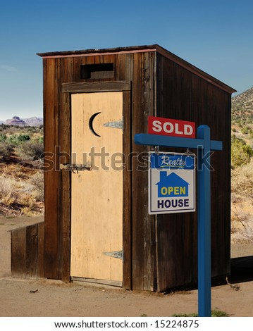 A realestate sign showing a dumppy out-house sold in the desert. - stock photo