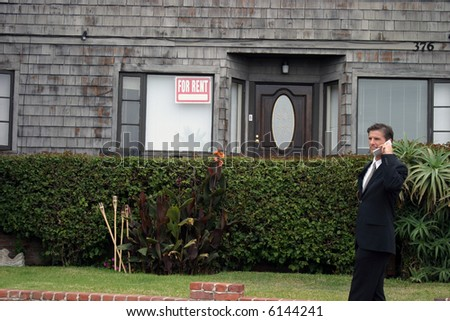 a realtor, or business man, or renter or building owner, talks on his cell phone while outside his home with a for rent sign in the window - stock photo