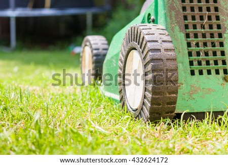 A rear view of a green lawnmower ready to cut the grass