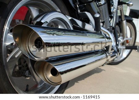 A rear view of a motorcycle with the focus on the chrome exhaust. - stock photo